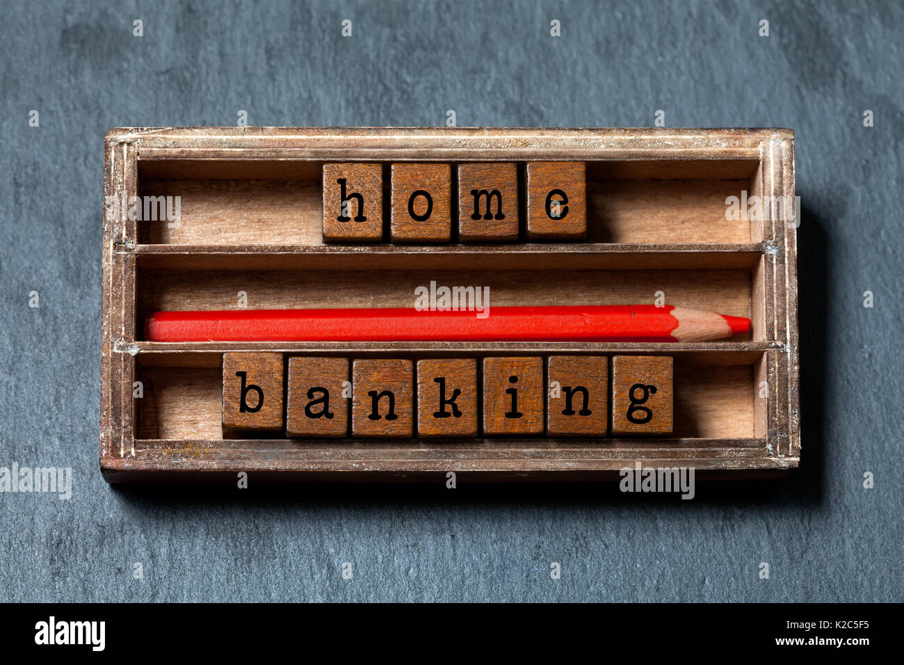 Home banking, budgeting concept image. Wooden boxes with letters, red pencil, aged box. Gray stone background, macro, Stock Photo