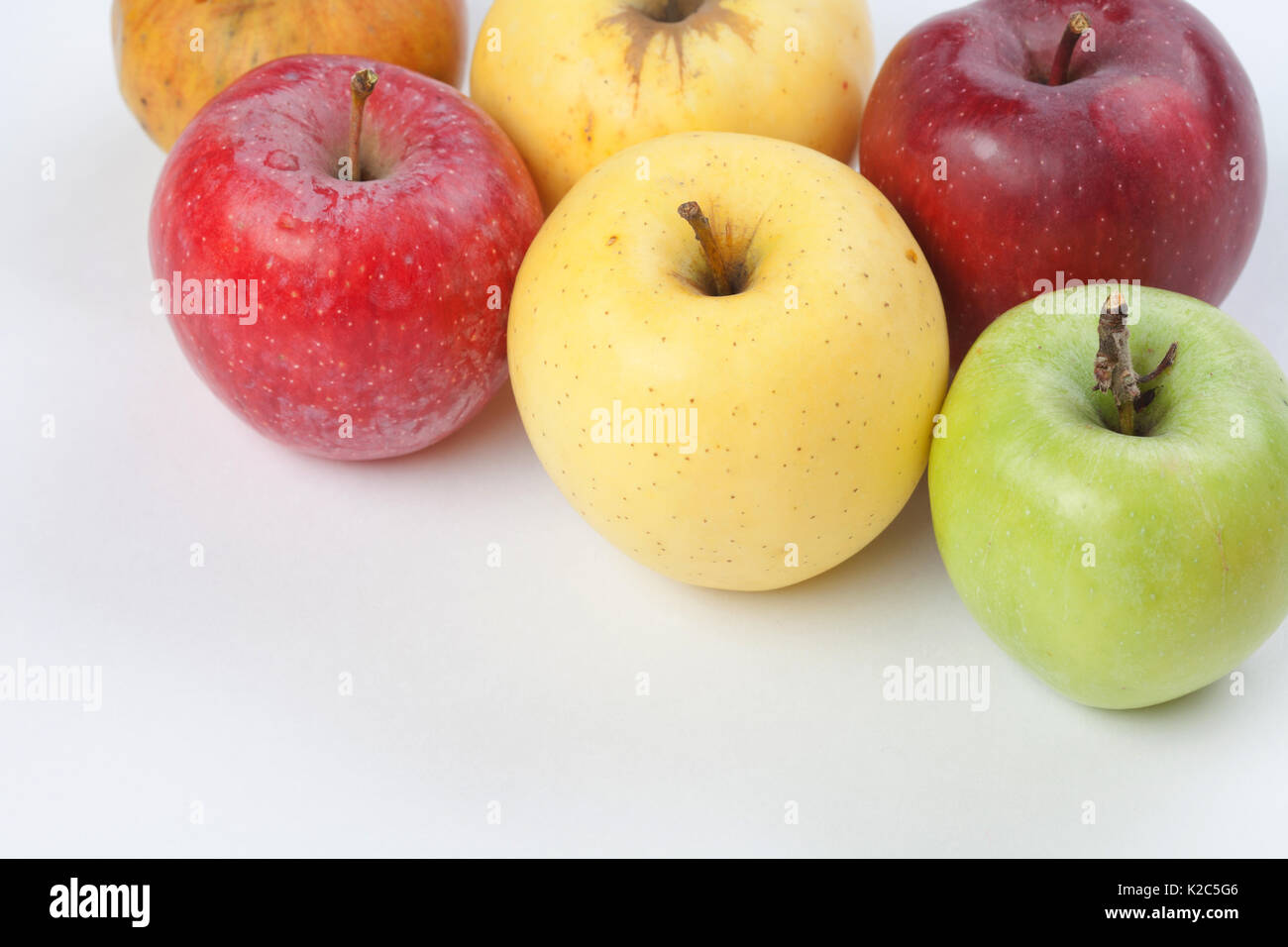 Colorful apples on white background. Fresh ripe apple fruits in different colors: red, yellow, green, orange. macro view. - Stock Image