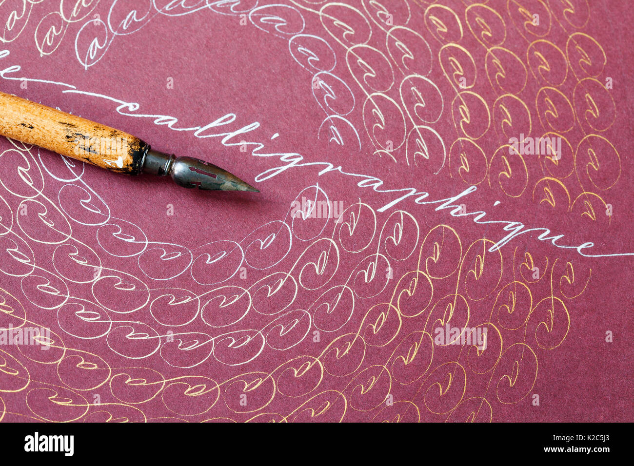 Aged fountain pen, artistic frame with letters A. Word Calligraphique concept. bronze silver ink. pink paper background. macro view, shallow depth of field - Stock Image
