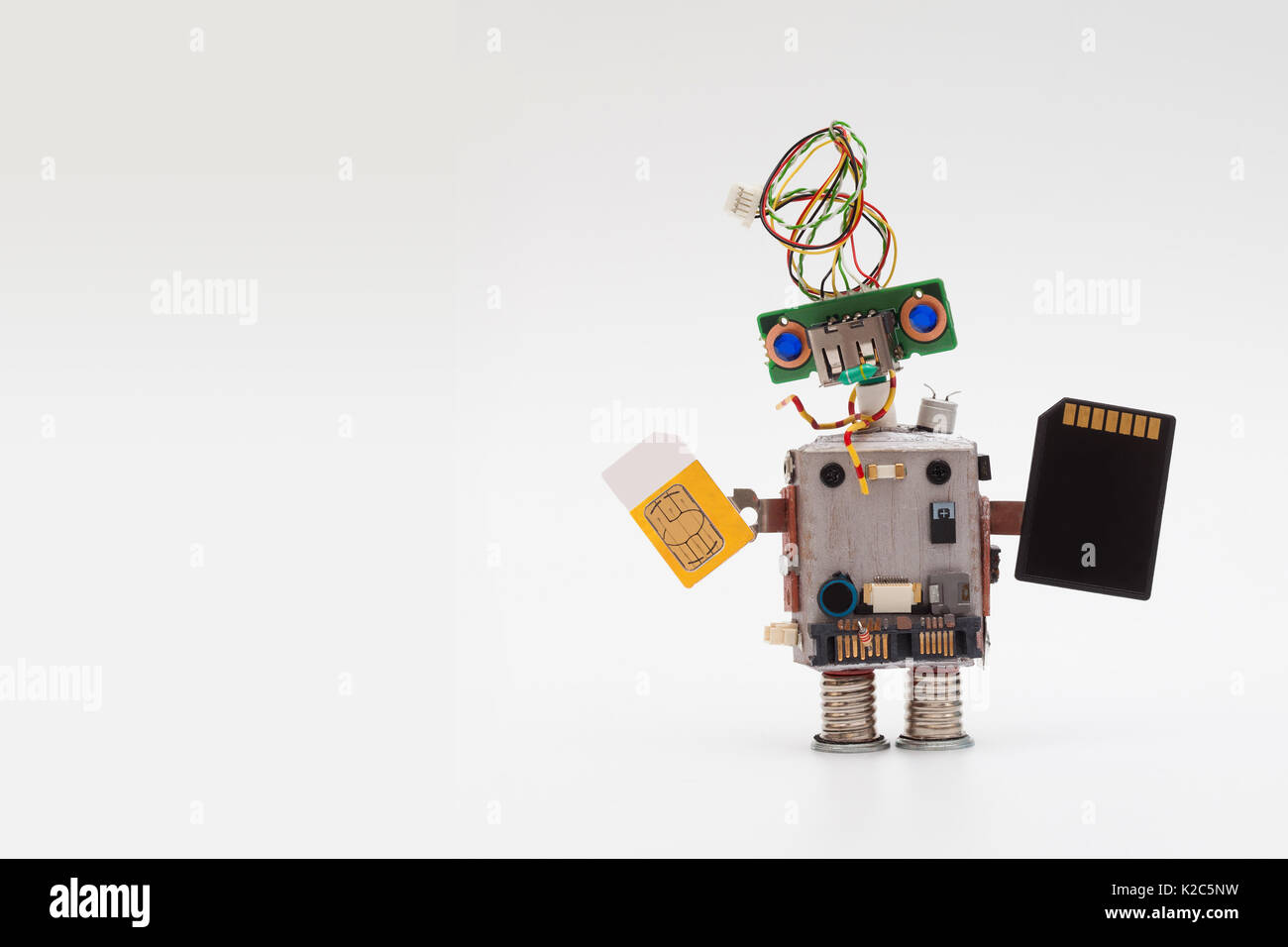 Retro style robot concept with yellow sim card and black microchip. Circuits socket toy mechanism, funny head, colored blue eyes. Copy text, light gradient background - Stock Image