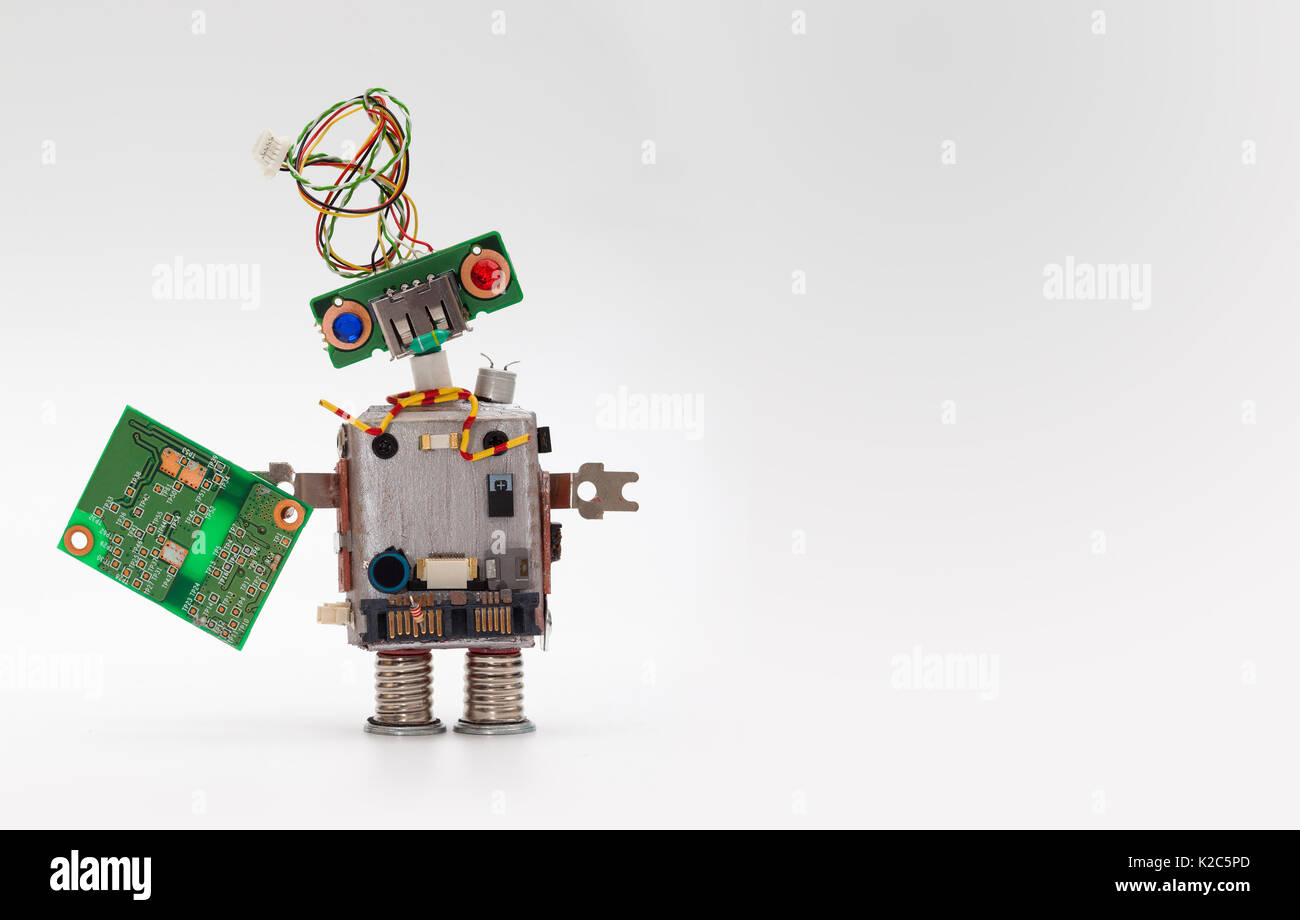 Robot with chip board. Computer accessories toy mechanism, funny head, electrical wire hairstyle, colorful blue red eyes. Copy space, gray background - Stock Image