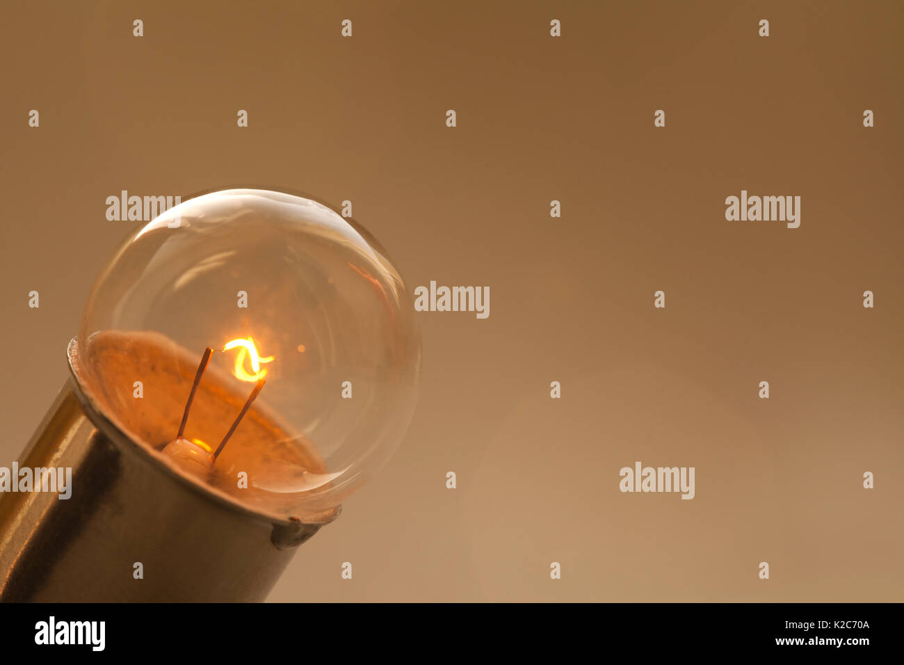 Glowing light bulb on gold brown background. Retro style lamp with ideal spherical surface and filament element. Macro view, copy space - Stock Image