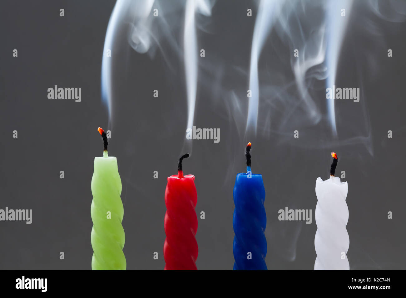 Colorful extinguished candles with white smoke on gray background. four pieces: green, red, blue, white. fading, finishing concept. soft focus macro view - Stock Image