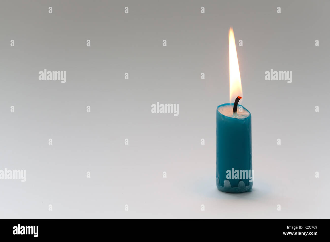 Burning candle with natural flame. Turquoise color. Simplicity concept Life symbol. Close-up, Shallow depth of field. gradient gray background. copy space - Stock Image