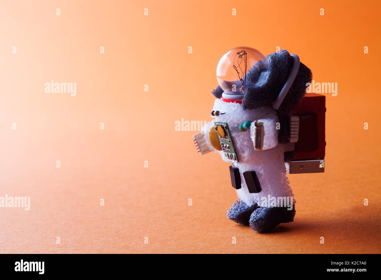 Spaceman light bulb character dressed in spacesuit and astronaut ammunition. Cosmonaut walking abstract orange planet background. creative cosmos concept. copy space - Stock Image