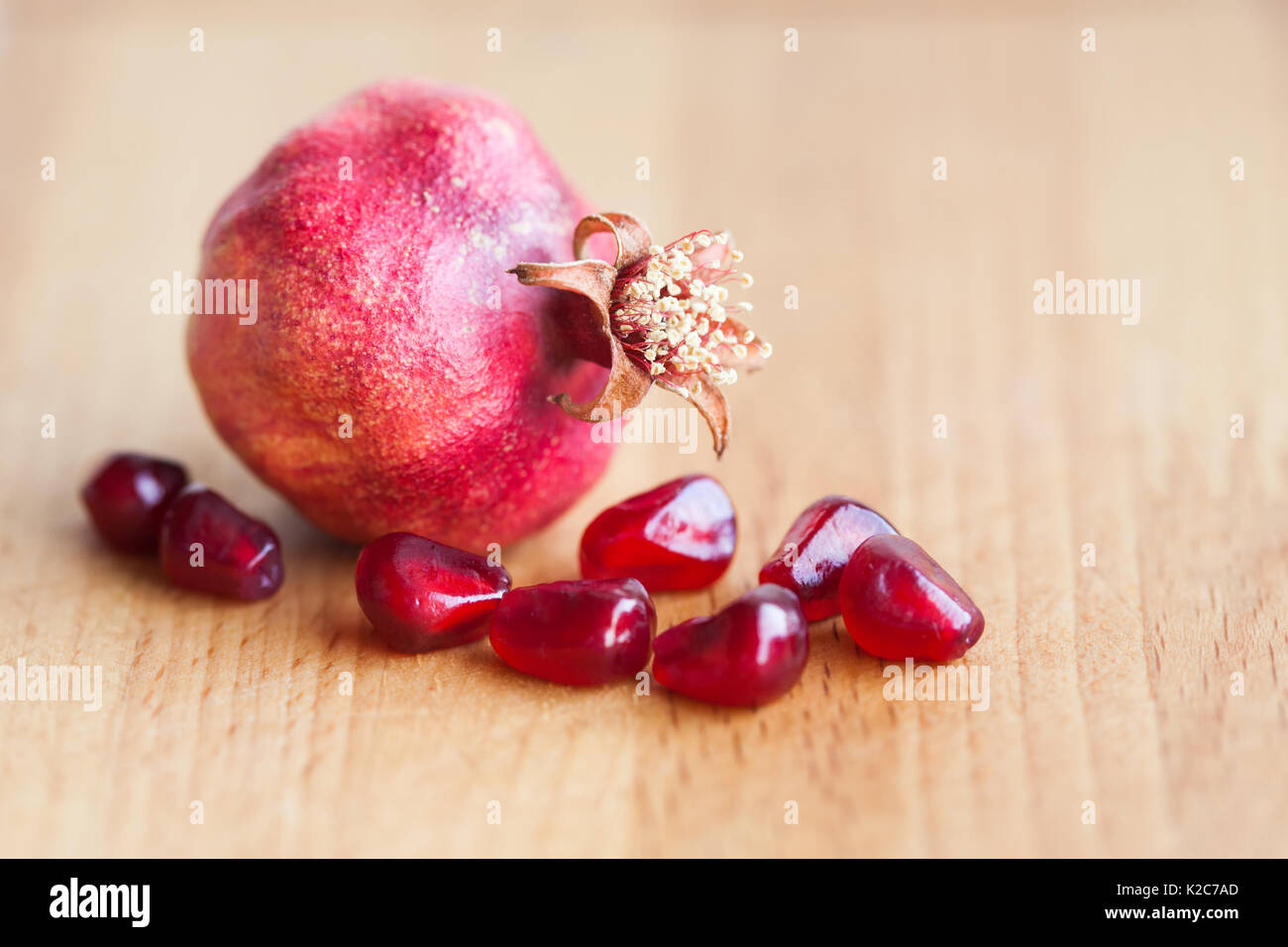 Pomegranate with seeds on wooden background. shallow depth of field - Stock Image