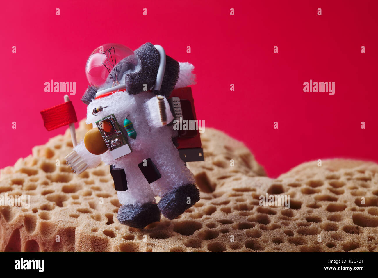 Spaceman explores red planet Mars. Light bulb character dressed in spacesuit and astronaut ammunition. Cosmonaut with flag walking abstract landscape. creative astronomic concept. Horizontal - Stock Image