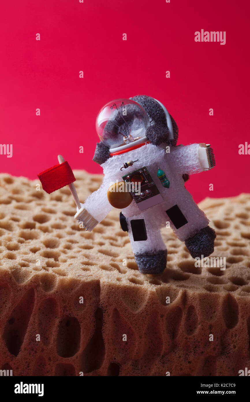 Walking astronaut, red background. Light bulb character dressed in spacesuit and spaceman ammunition. Cosmonaut with flag at the edge planet landscape. cosmos exploration concept. - Stock Image