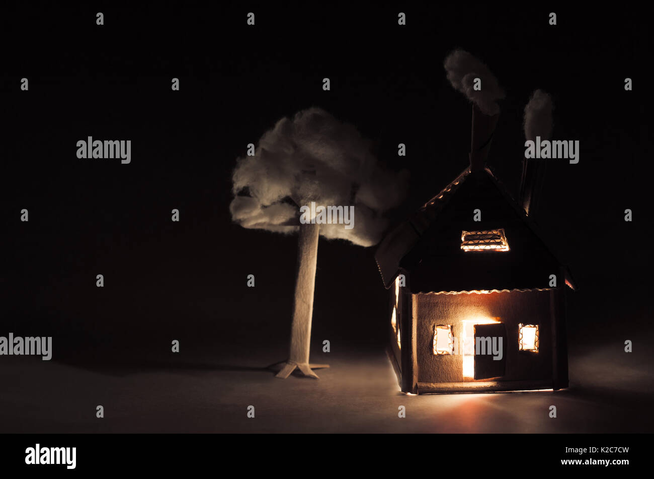 Cardboard house with  luminous windows, chimney and white smoke in the darkness. night time - Stock Image