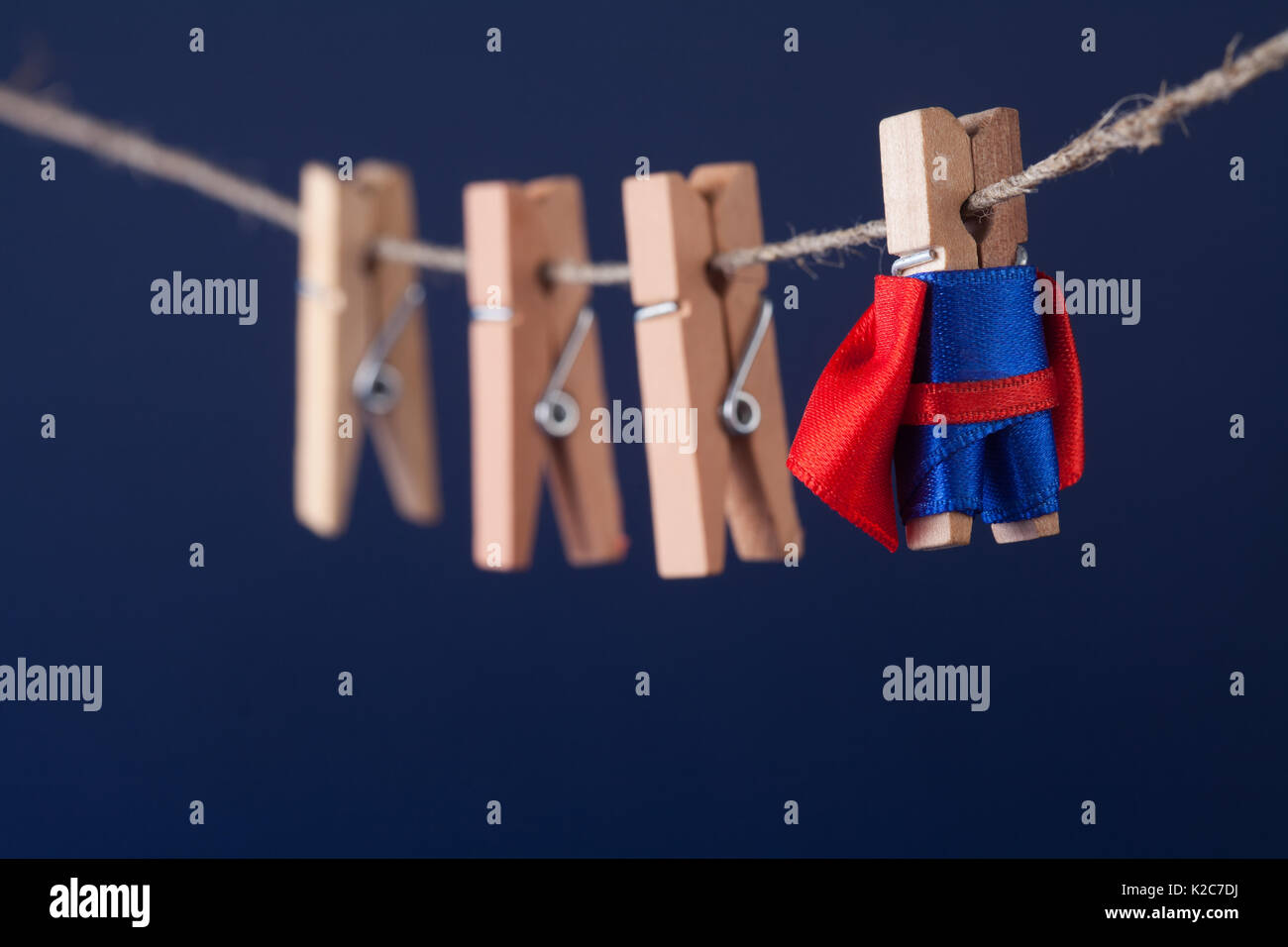 Powerful super hero conceptual photo with superstar clothespin character in blue suit red cape. leadership and wooden clothespins team at work. Dark background. soft focus. macro view - Stock Image