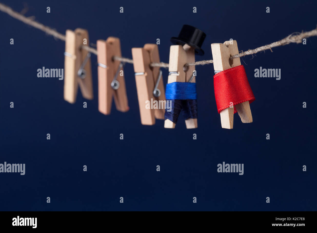 Creative design clothespin characters man in suit, woman red dress hanging on rope. concept with clothesline and dark blue background. Macro view, shallow depth of field - Stock Image