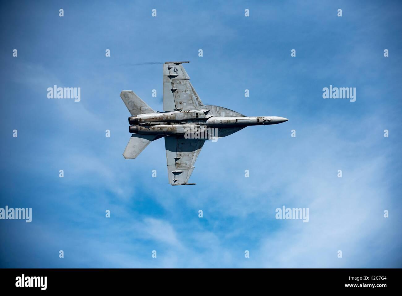A U.S. Navy F/A-18E Super Hornet jet fighter aircraft flies over the U.S. Navy Nimitz-class aircraft carrier USS Stock Photo