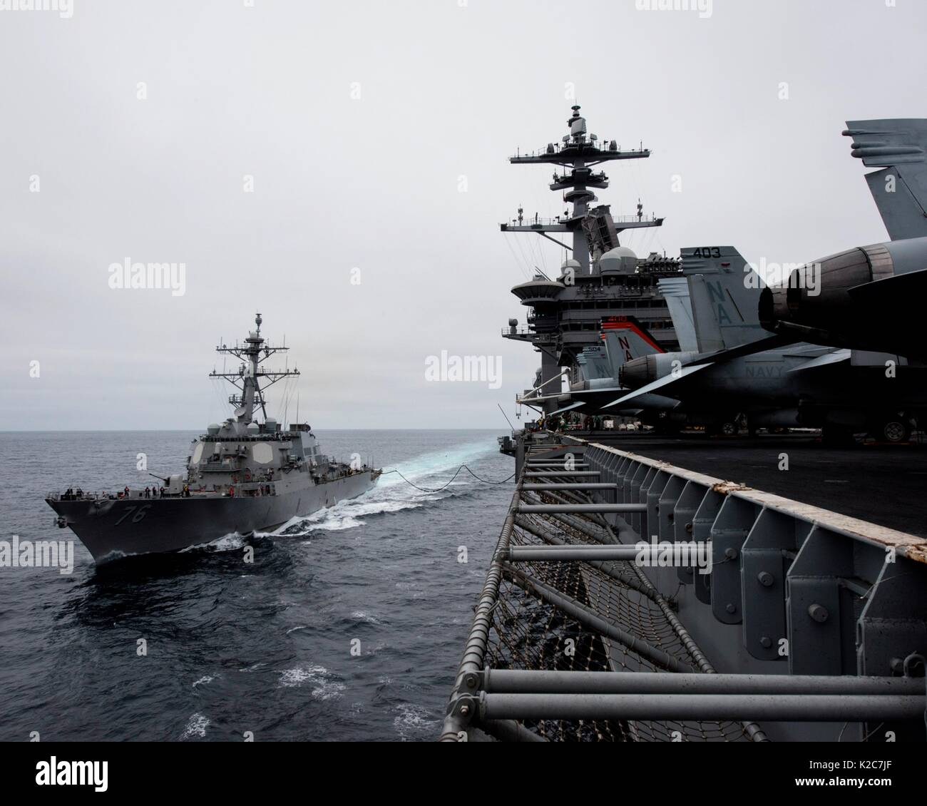 The U.S. Navy Arleigh Burke-class guided-missile destroyer USS Higgins (left) steams in formation alongside the U.S. Navy Nimitz-class aircraft carrier USS Theodore Roosevelt August 14, 2017 in the Pacific Ocean. - Stock Image