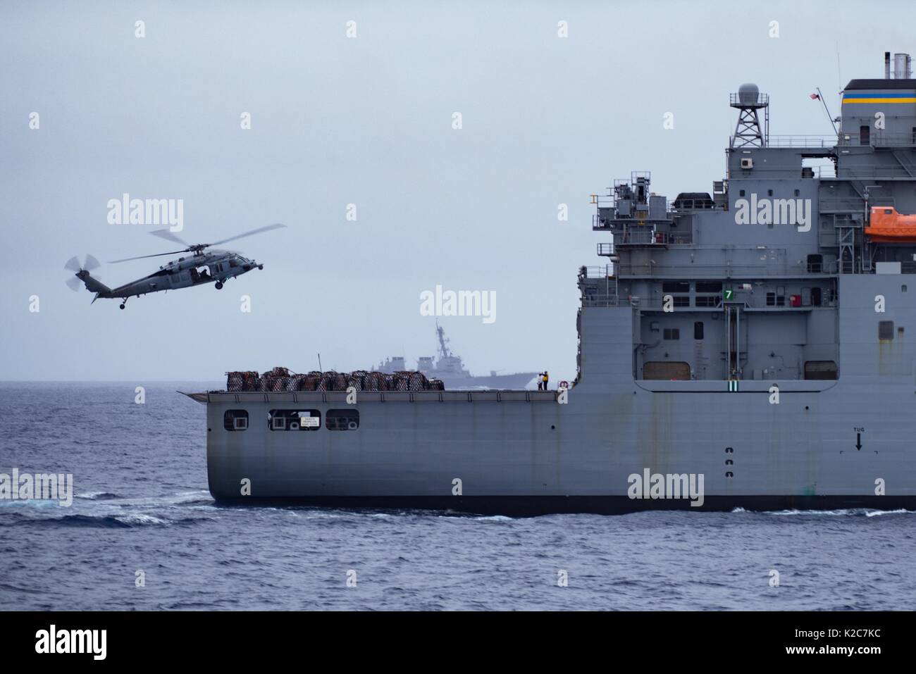 A U.S. Navy MH-60S Seahawk helicopter picks up supplies from the U.S. Navy Lewis and Clark-class dry cargo ammunition ship USNS Matthew Perry August 15, 2017 in the Pacific Ocean. - Stock Image