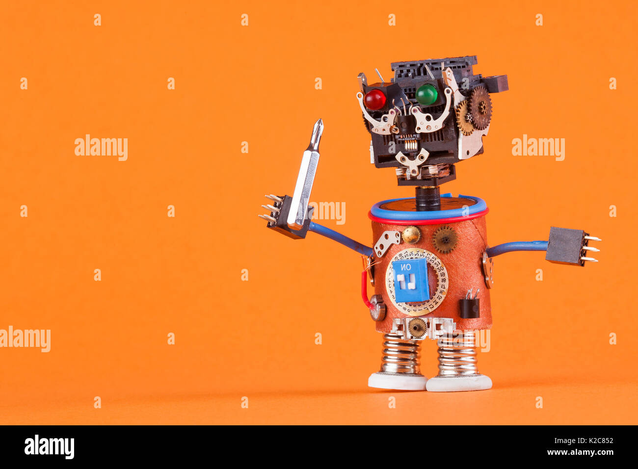 Funny robot toy with screw driver. Cute character black plastic head, colored green red eyes lamp, blue wire hands. Stock Photo