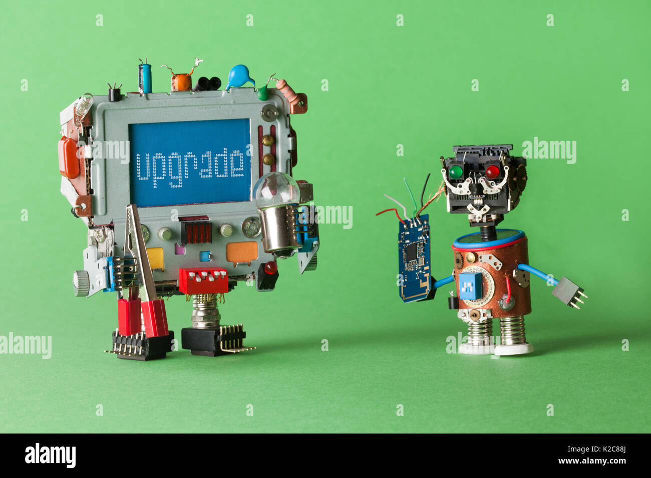 Upgrade computer concept. Handyman technician robot with circuit in hand and monitor robotic character, warning message on blue screen. green background macro - Stock Image