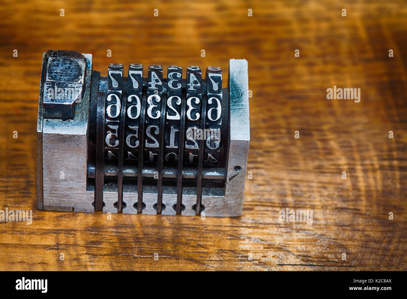 Cliche stamp with numbers Vintage metallic counter mechanism on wood patten table. Calculator conceptual image. close-up, shallow depth of field, soft focus - Stock Image