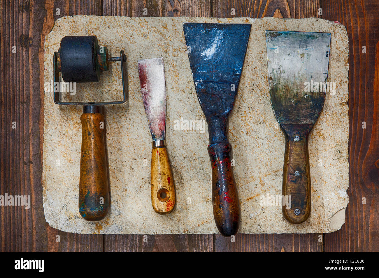 Retro design tools for artist workshop: rubber roller, different size putty knives on stone plate and wooden background. Techical service diy tools, decorator accessories concept. soft focus, up view - Stock Image