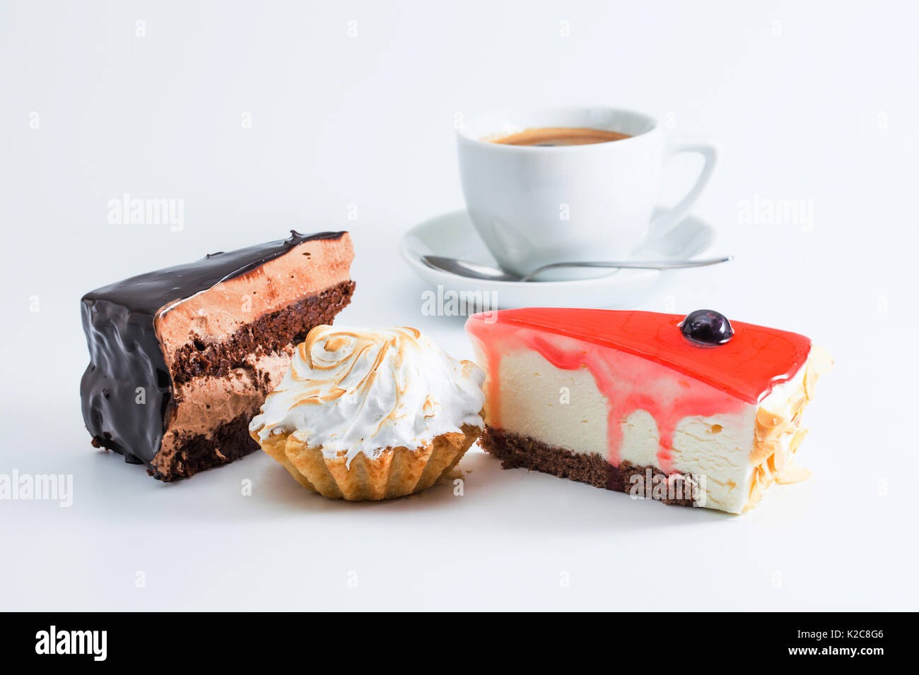 Dessert set with cup coffee on white background. Three piece of cakes chocolate red jam mousse cheesecake cupcake Stock Photo