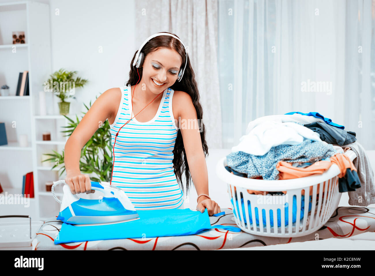 Young beautiful smiling woman ironing clothes and listening music on headphones. - Stock Image