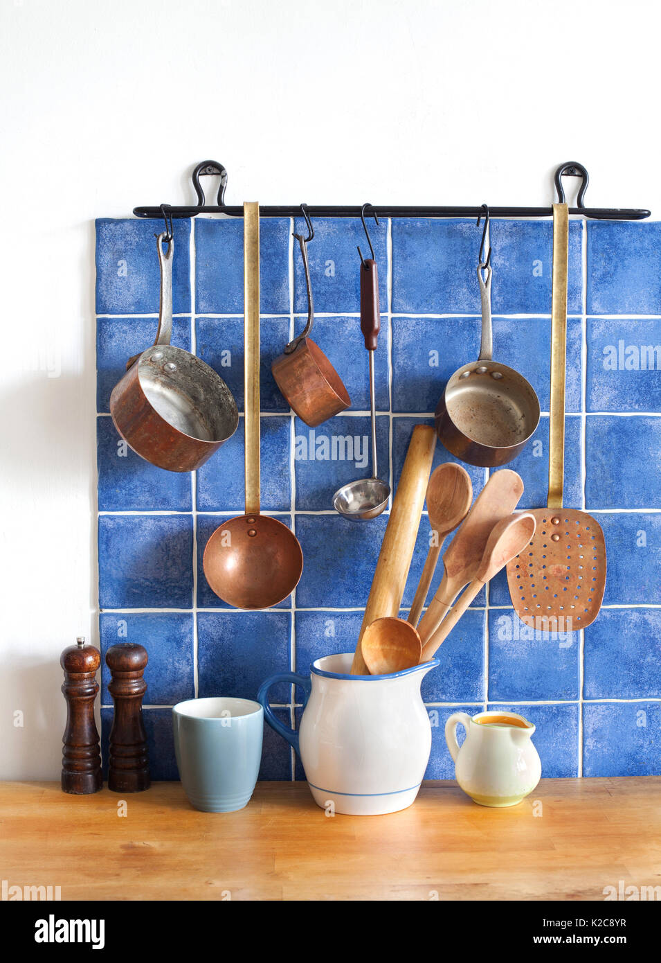 Retro design kitchen interior with accessories. Hanging copper kitchenware set. Pot, stewpot, spoon, skimmer, ladle. Different sizes pitchers, cup. wooden table. Blue tiles background - Stock Image