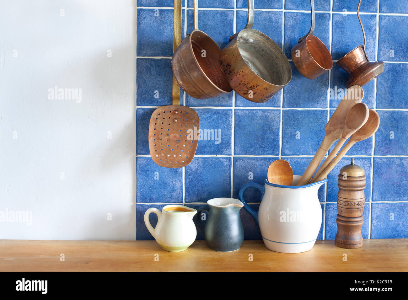 Retro design kitchen interior with accessories. Hanging copper kitchenware set. - Stock Image