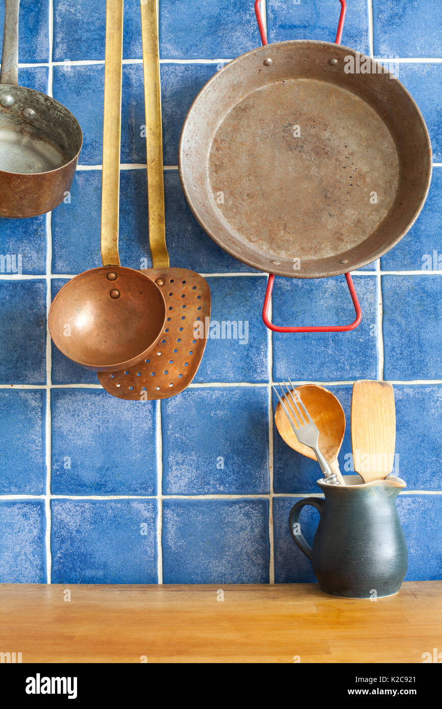 Vintage style kitchen accessories. Old utensils pan ladle pitcher with spoon, spatula. Wooden table and blue tile background. - Stock Image