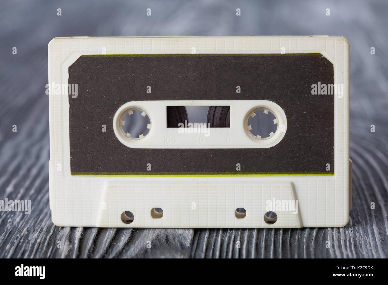 Vintage compact cassette with magnetic tape recording format for audio and playback. gray wooden background. Soft focus. macro view - Stock Image