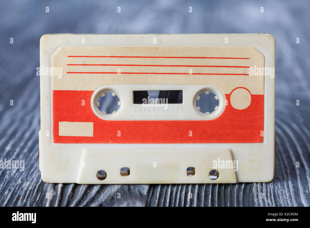 Red compact cassette with magnetic tape format for audio recording and playback. gray wooden background. Soft focus. - Stock Image