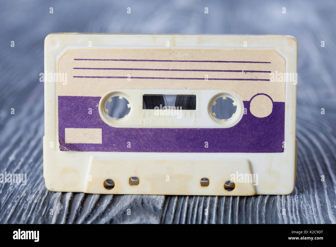 Violet compact cassette with magnetic tape format for audio recording and playback. MC on gray wooden background. Soft focus. - Stock Image