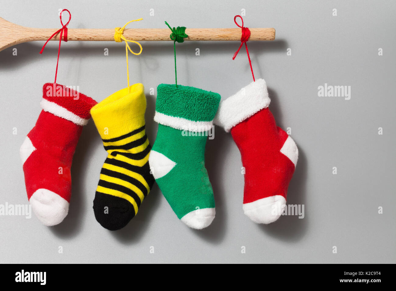 Merry Xmas text invitation card. Hanging Christmas socks on gray beige background. Colorful stocking decoration - Stock Image