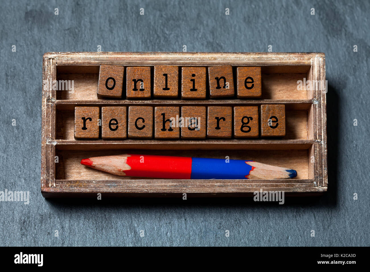Online recharge concept. Vintage box, wooden cubes with old style letters, colorful red blue pencil. Gray stone textured background. Close-up, up view, soft focus. - Stock Image