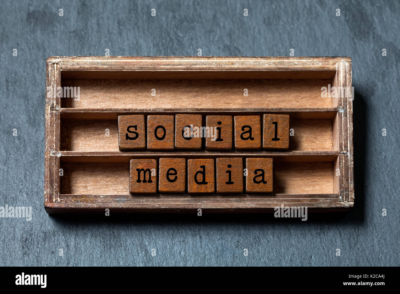 Social media retro style text. Vintage blocks with letters, aged wooden box frame. Gray stone background, macro, soft focus - Stock Image