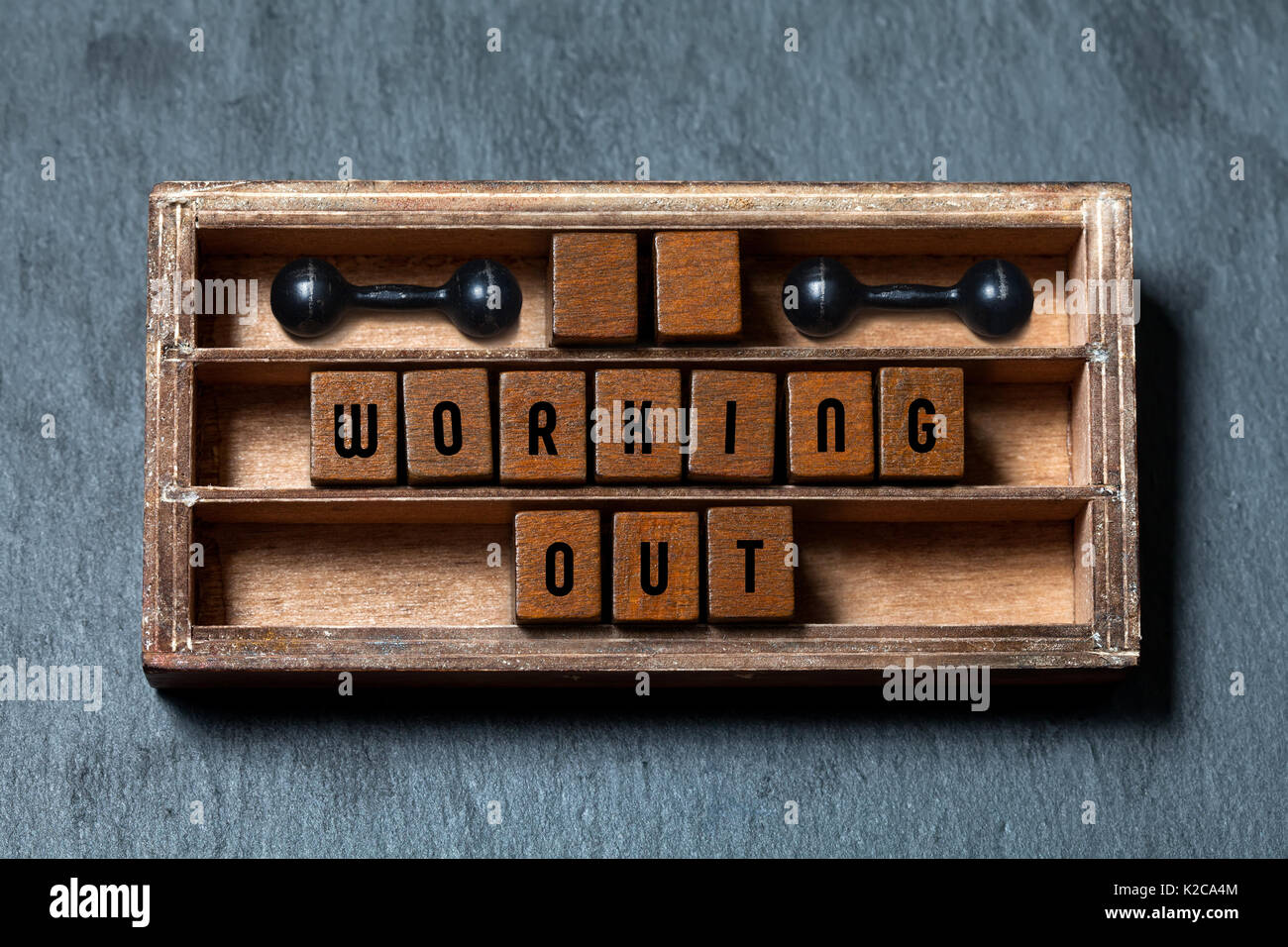 Working out gym concept heading. Aged box, wooden cubes with old style letters, black dumbbells. Gray stone textured background. Close-up, up view, soft focus. - Stock Image