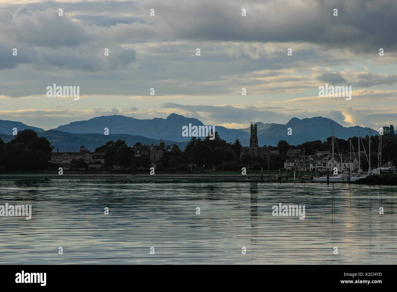 Rhu Marina in silhouette at dusk twilight with clouds and a mountains background light reflecting off calm windless sea taken from the water - Stock Image