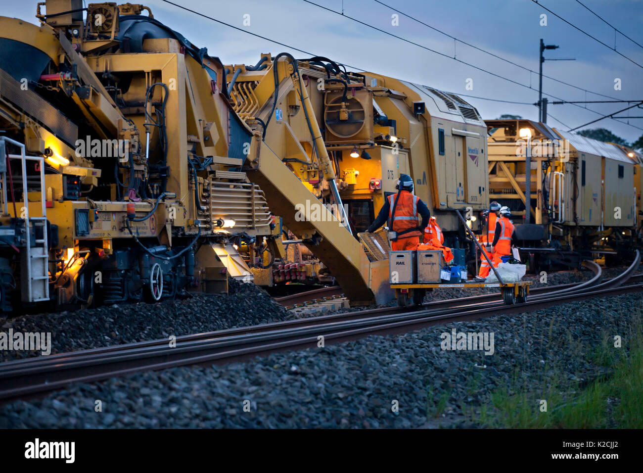 Workmen waiting for rails to be welded before completing last piece of relaying with a Matisia  track renewal train on the West Coast main line - Stock Image
