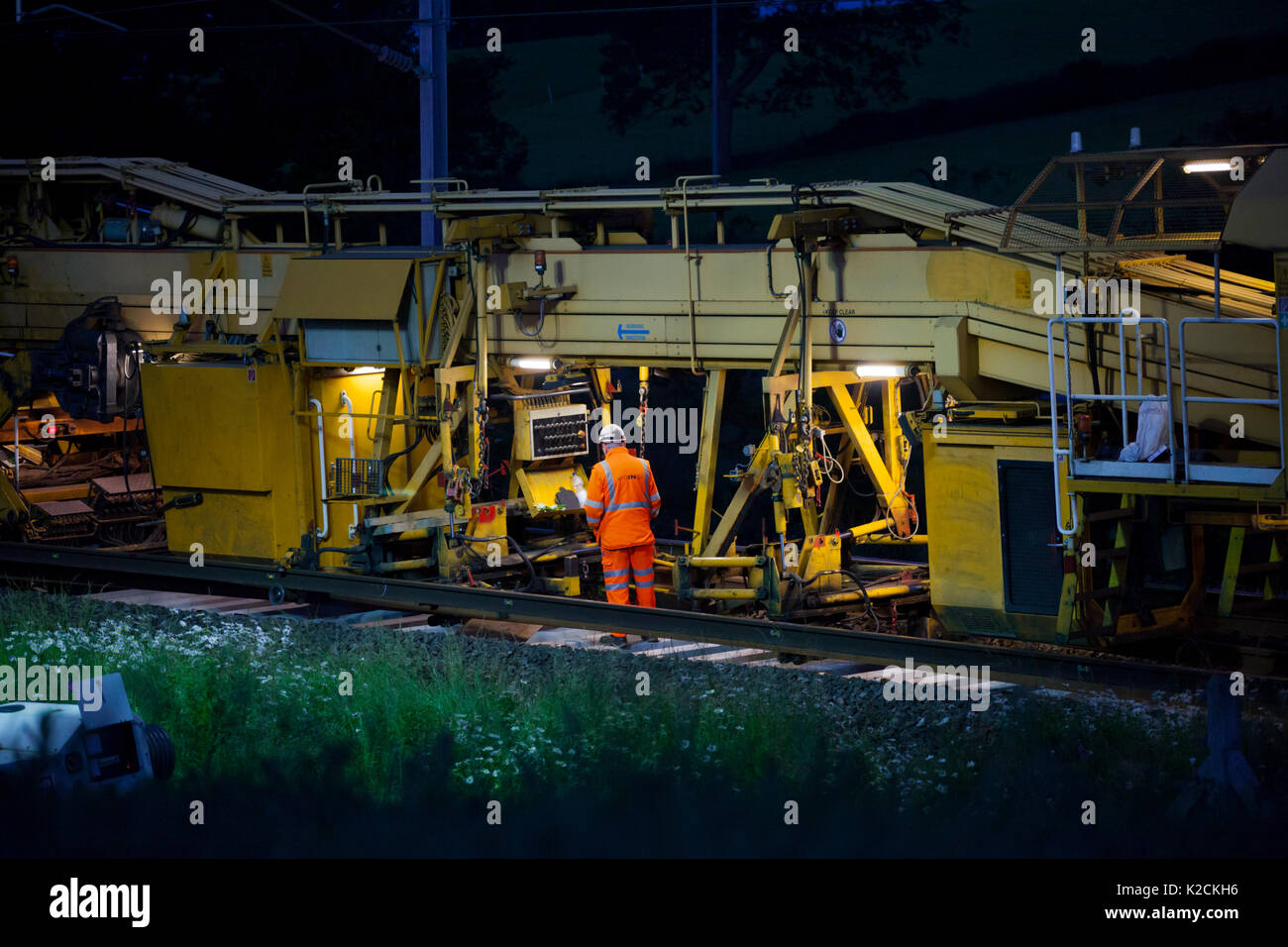 operative working on a Matisa track renewal train relaying track on the West Coast mainline in Lancashire during an overnight engineer's possesion - Stock Image