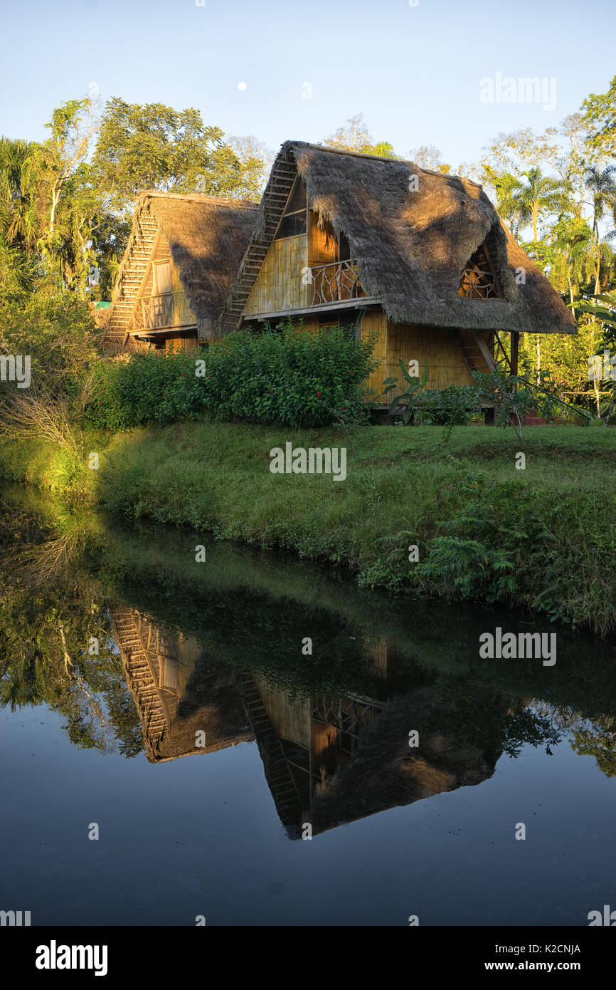 June 6, 2017 Puerto Misahualli: eco lodge built from bamboo in the jungle reflecting nto water at sunset - Stock Image