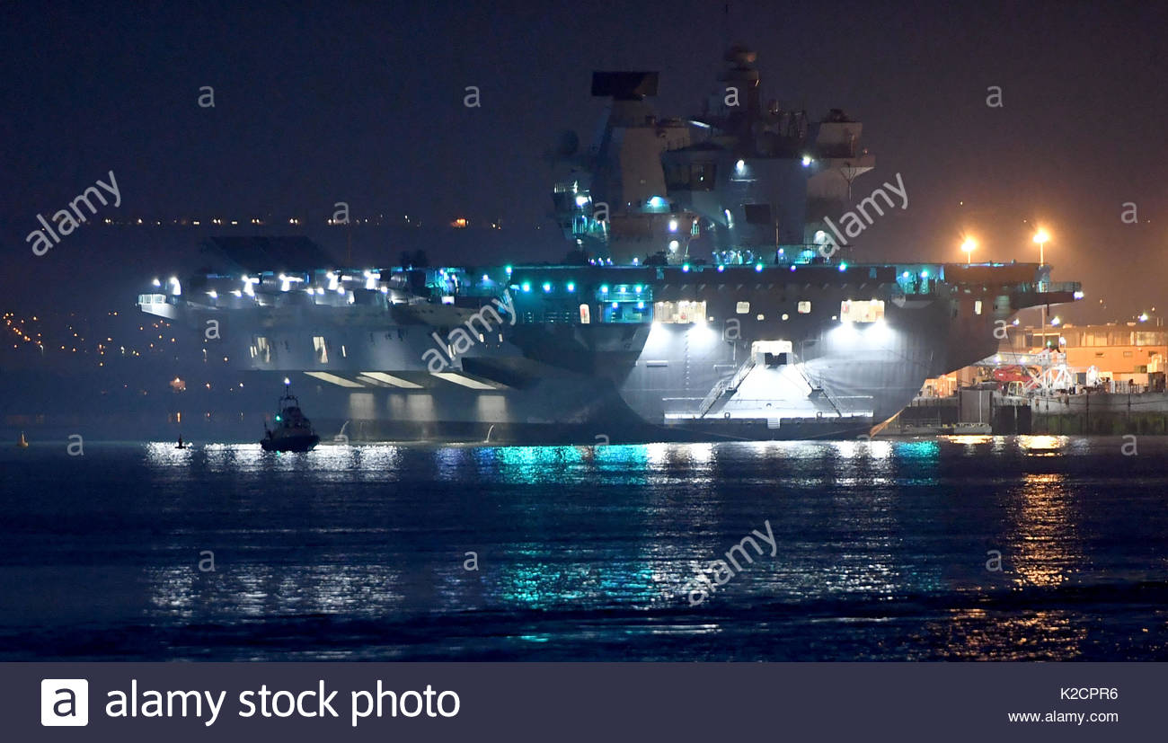 29/9/17 -  HMS Queen Elizabeth lights up Portsmouth Harbour, docked at her home port at Portsmouth Naval Base.  Whilst in dock she is powered by a sub - Stock Image