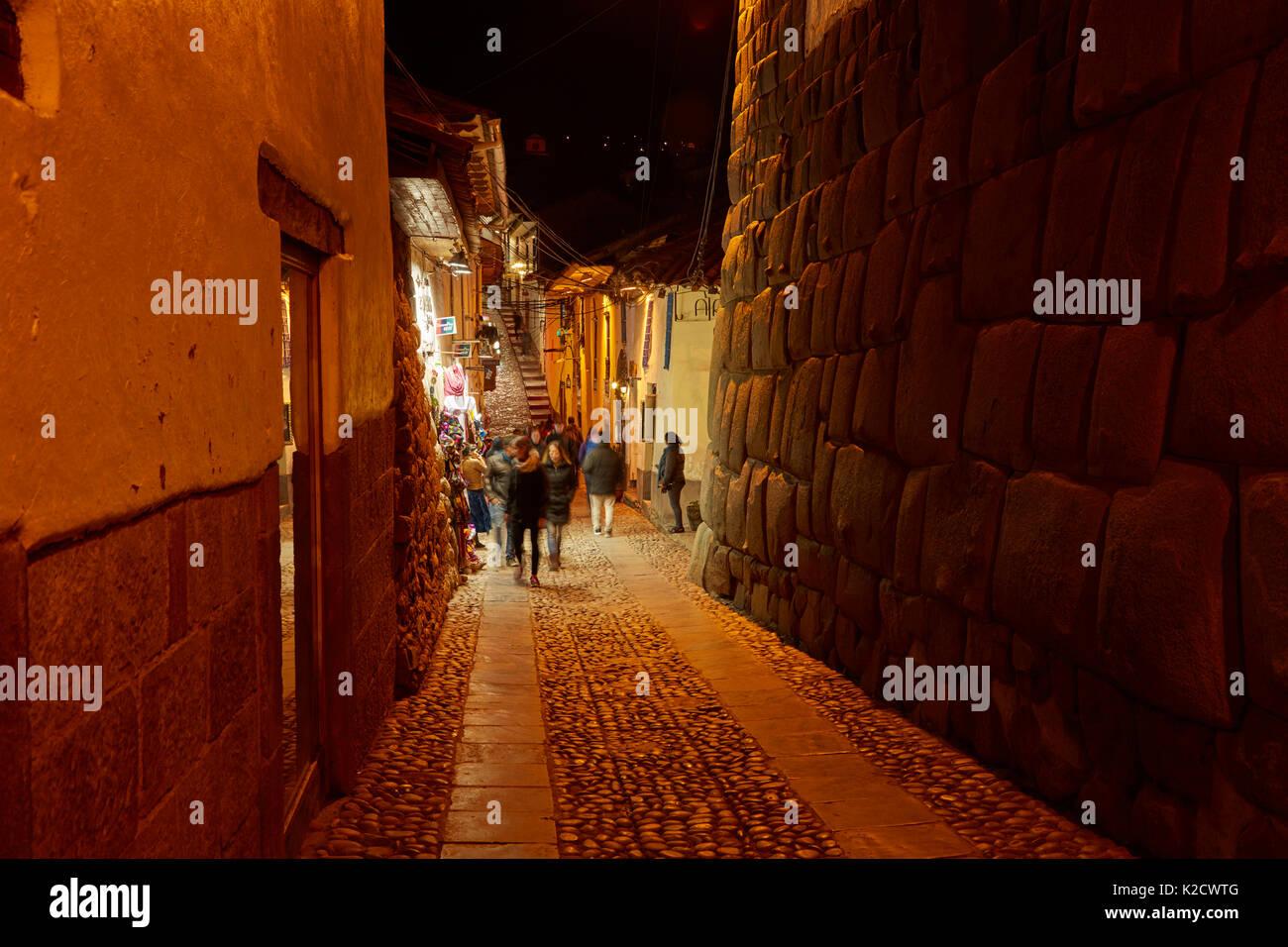 Historic Inca stonework on Calle Hatunrumiyoc at night, Cusco, Peru, South America - Stock Image