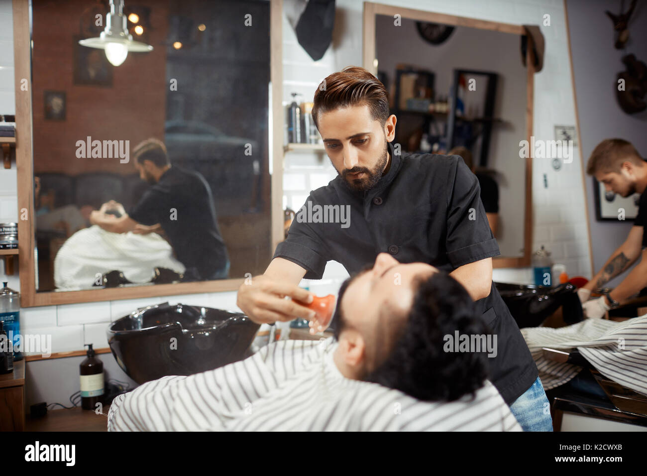Hairstylist in black combing out bread for brunet at barbershop. - Stock Image