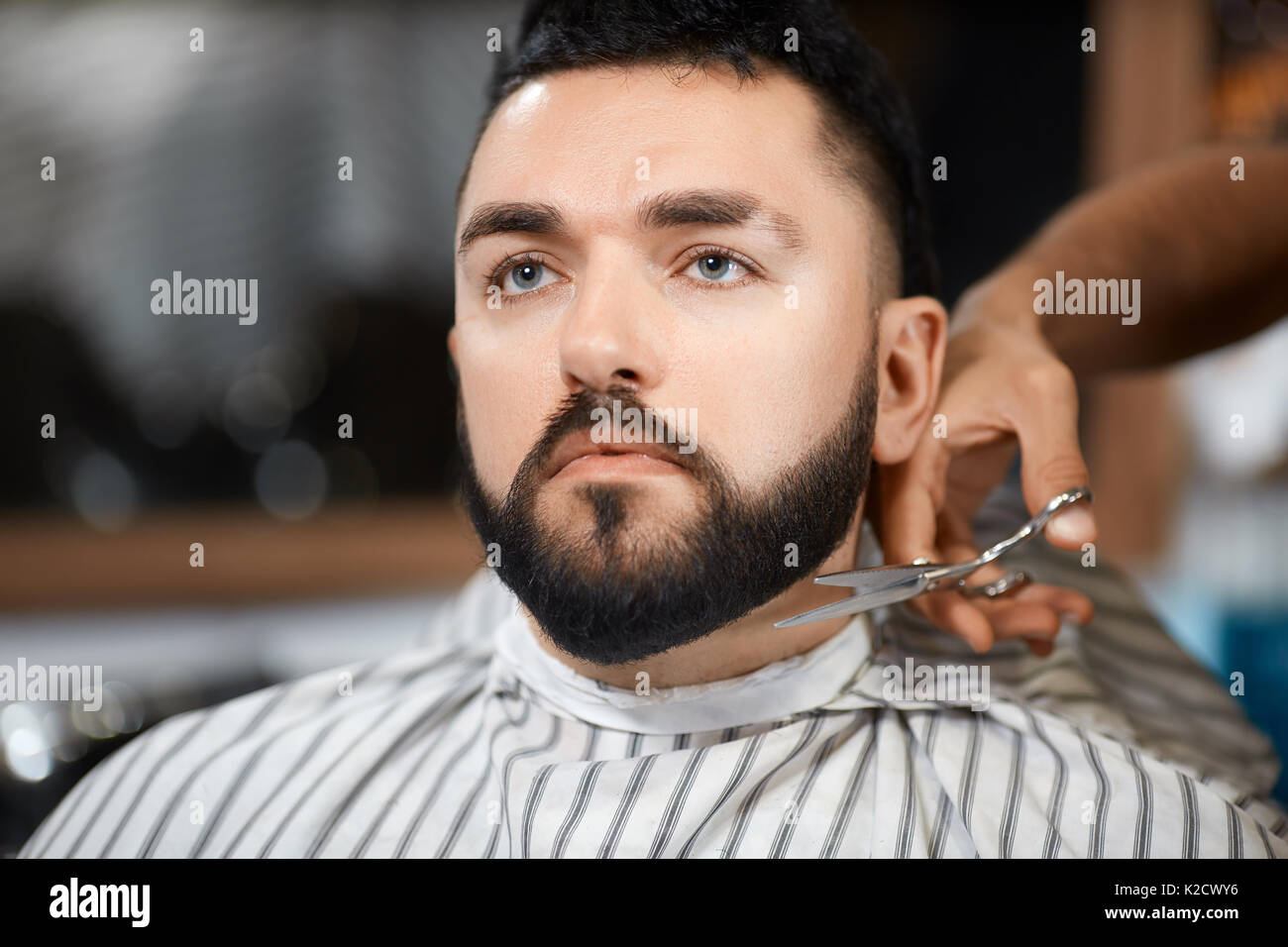 Hairdresser cutting bread with scissors for brunet client. - Stock Image