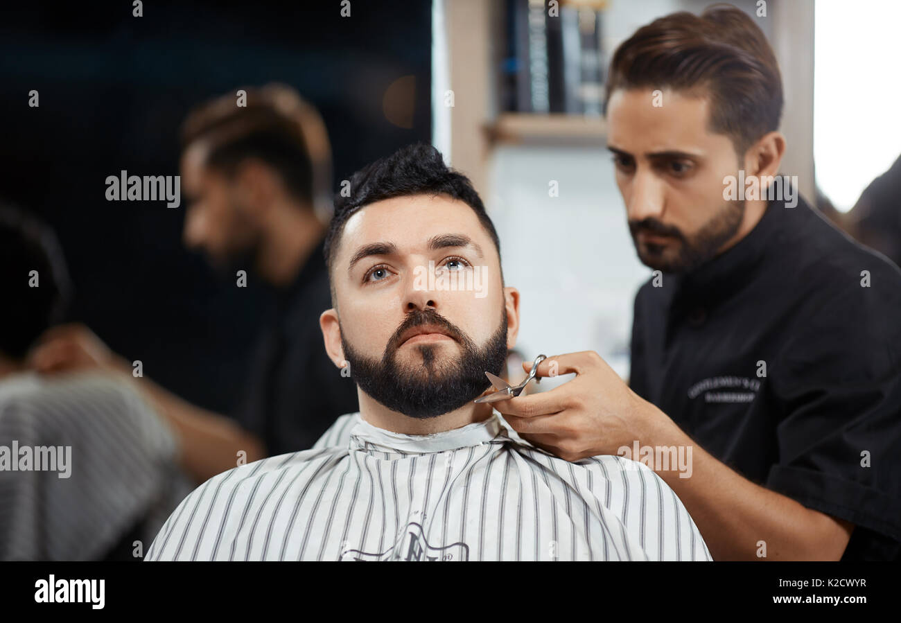 Hairdresser cutting bread with scissors for brunet man in barbershop. - Stock Image