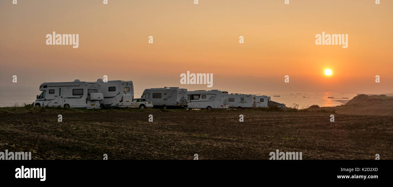 Motorhomes parked along the Normandy coast at sunset with view over the sea, France, September 2014. - Stock Image