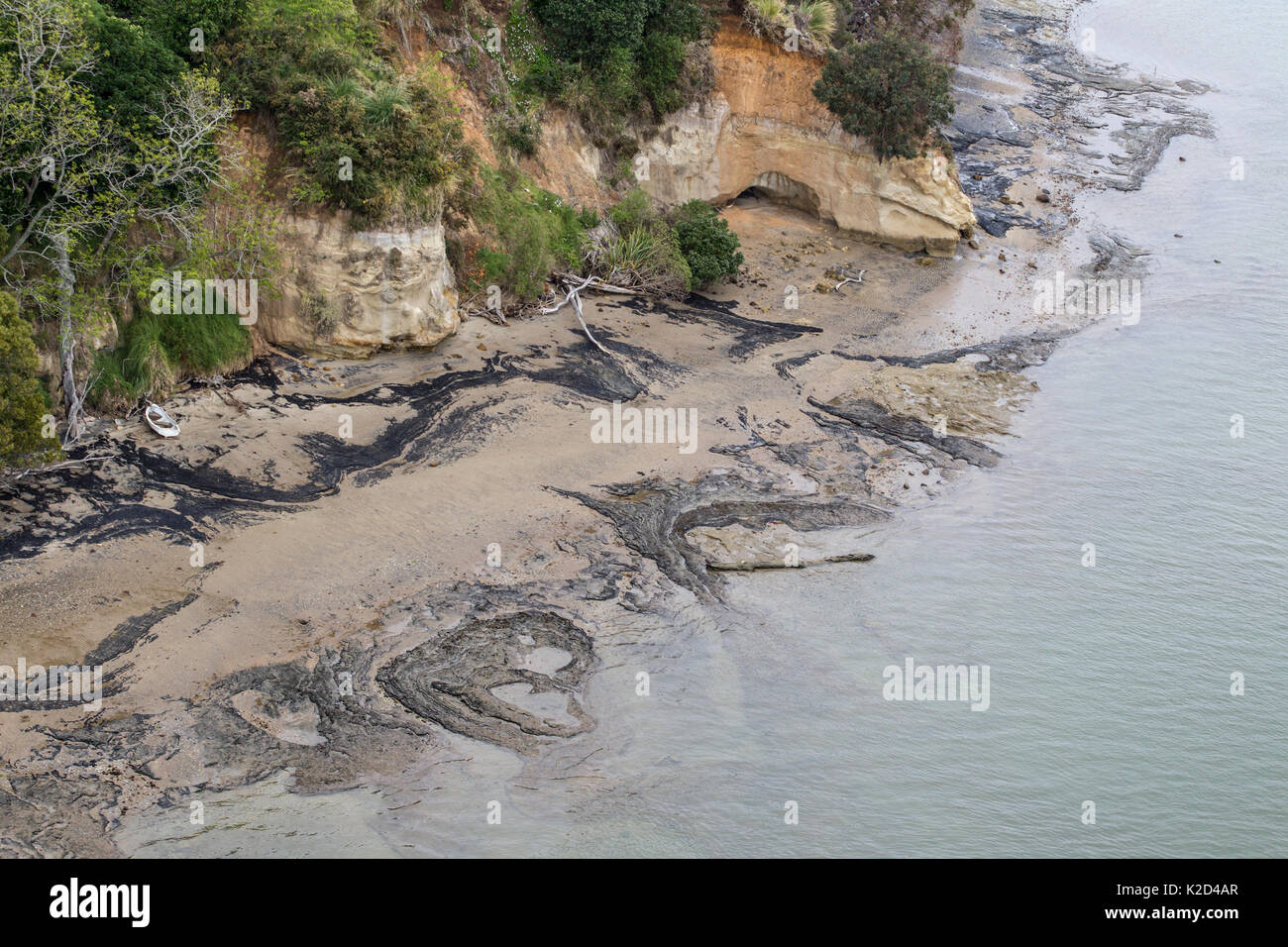 Aerial view of coast line with dark rocks and rowing boat, off Port of Tauranga, Tauranga, Bay of Plenty, New Zealand, October 2011. - Stock Image