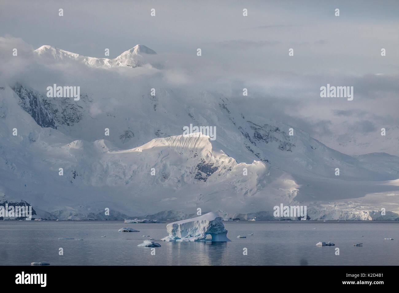 Low wispy clouds around mountains above Wilhelmina Bay, Antarctic Peninsula, Antarctica, January 2012. - Stock Image