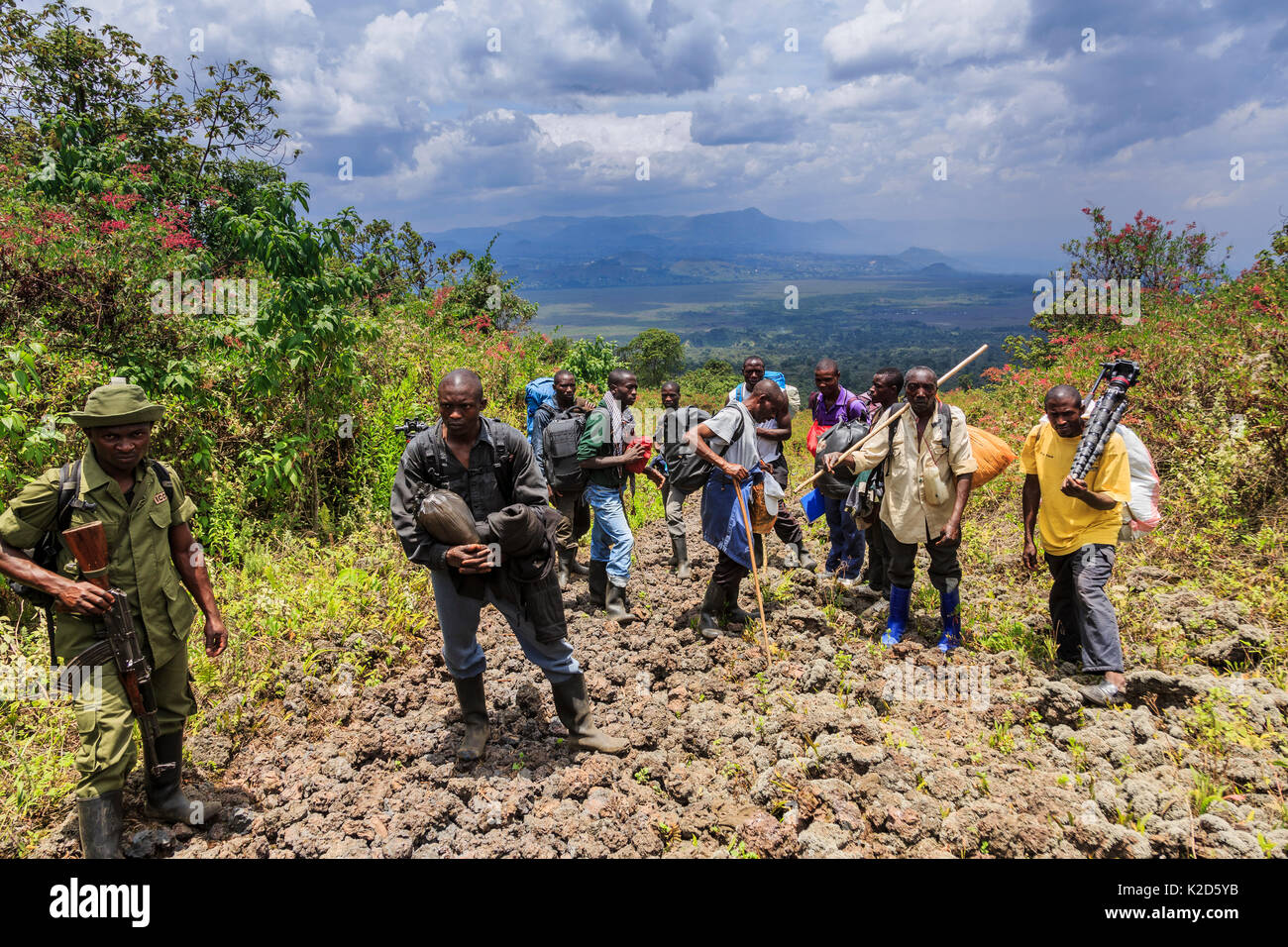 Virunga National Park guard with porters carrying equipment and supplies, on trail to Nyiragongo Volcano, Virunga National Park, North Kivu Province, Democratic Republic of Congo. September 2015. - Stock Image