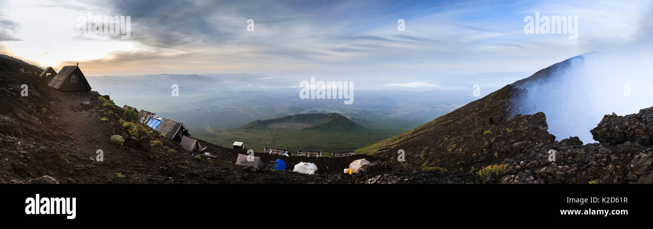 Makeshift camp at the summit of Nyiragongo Volcano. Next to the crater of the volcano, which has the largest active lava lake in the world. Virunga National Park, North Kivu Province, Democratic Republic of Congo. September 2015. Digital stitch. - Stock Image