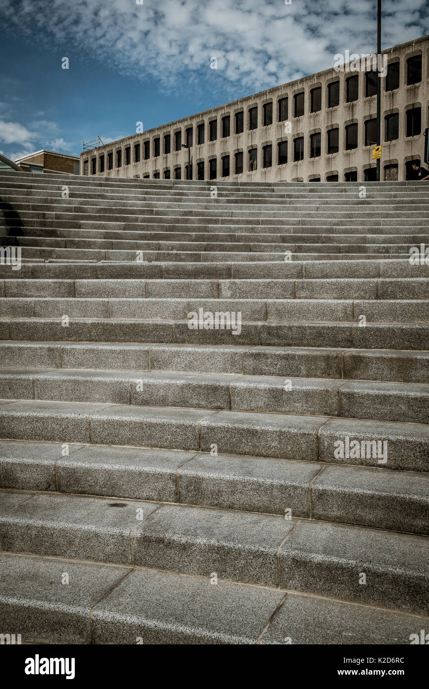 Concrete steps leading up towards an old concrete building with a sliver of cloudy blue sky - Stock Image