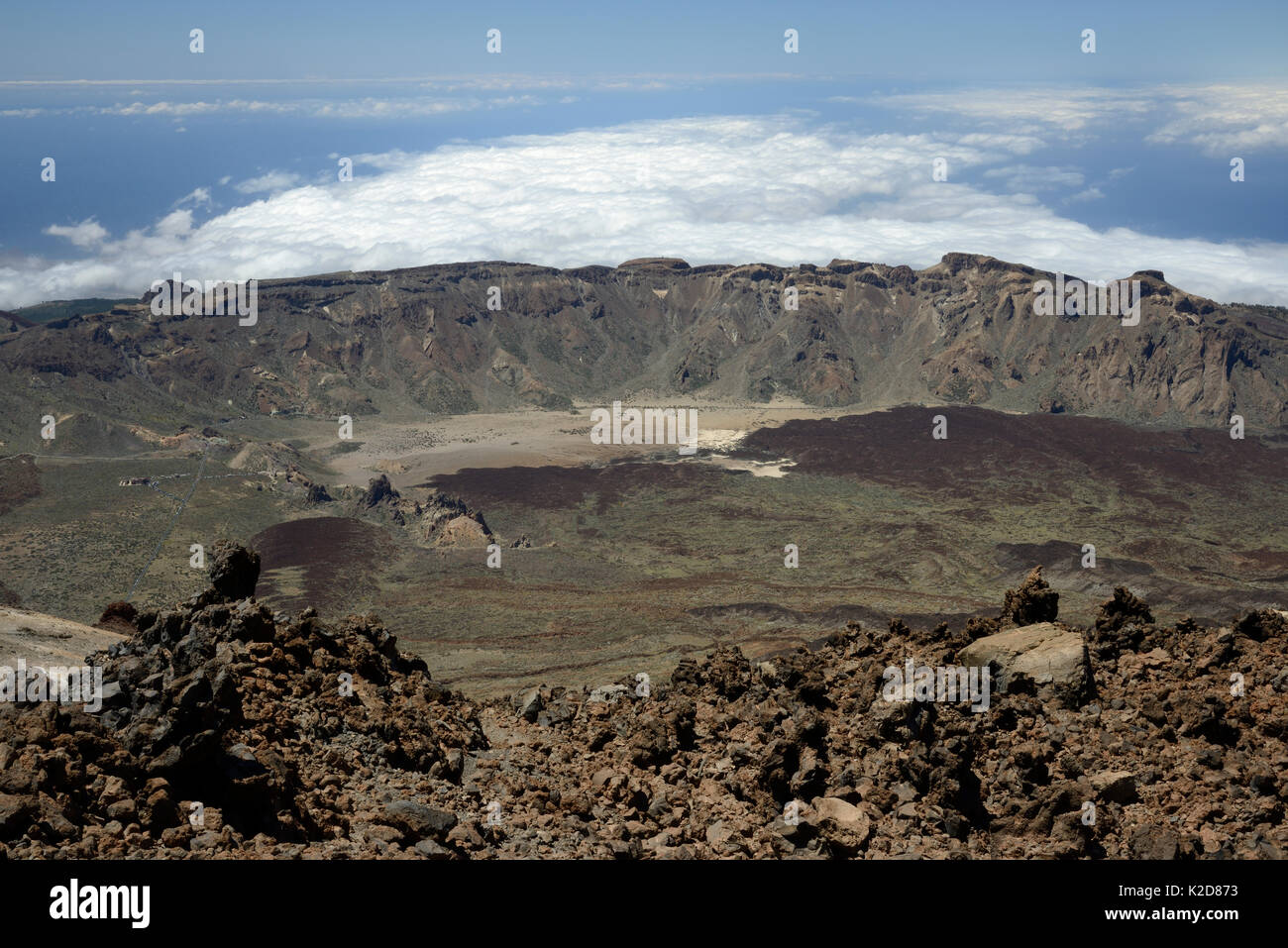 Overview of Las Canadas caldera from the 3718m summit of Mount Teide, the highest mountain in Spain, with old lava flows and pumice deposits, with clouds over the sea in the background, Tenerife, May. - Stock Image